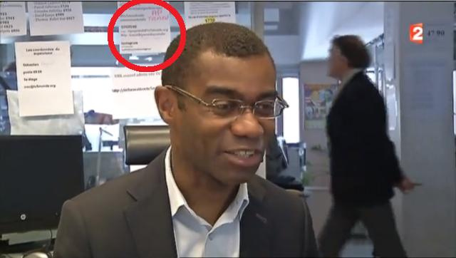 Empregado da TV5Monde concede uma entrevista com um cenário de senhas ao fundo.
